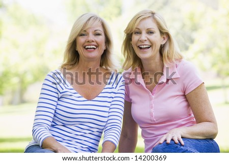 Two women sitting outdoors smiling - stock photo