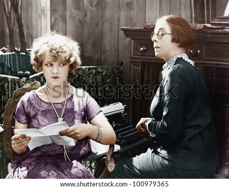 Two women sitting together working - stock photo