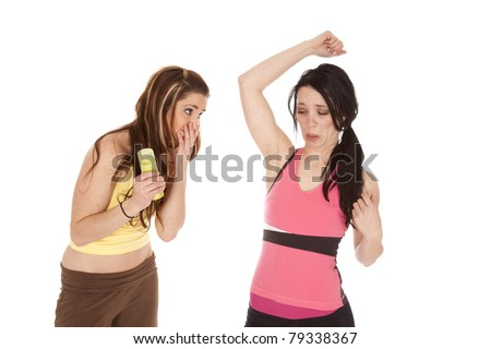 Two women smelling armpit and not liking what they are smelling.