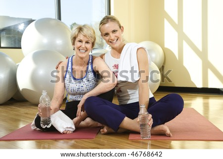 Two women smile towards the camera while sitting on the floor of a gym. One woman has her arm around the other and balance balls can be seen in the background. Horizontal shot. - stock photo