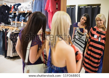 Two women smiling in front of the mirror in clothing store - stock photo