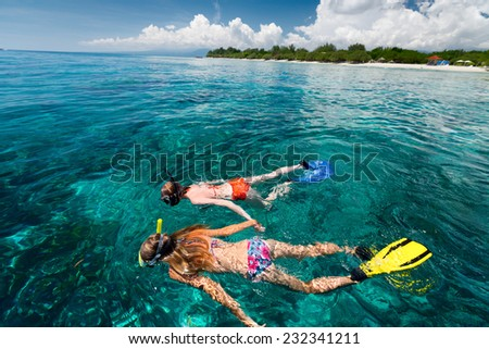 Two women snorkeling in the tropical sea at sunny day - stock photo