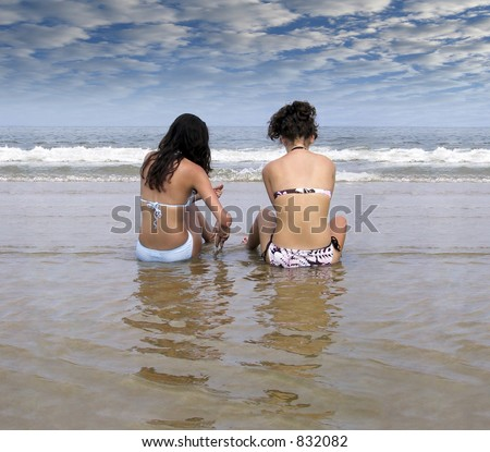 Two women soak in the sun and water - stock photo