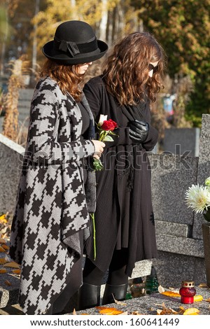 Two women standing above grave on sunny autumn day - stock photo