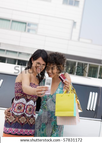 two women standing by limousine and taking picture on mobile phone. Vertical shape, waist up, copy space - stock photo