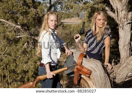 Two women standing together holding their weapons in their western outfits. - stock photo