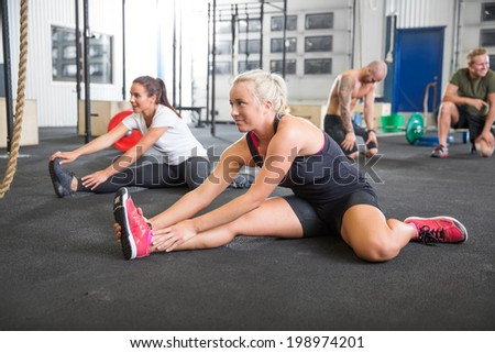 Two women stretching on the floor - stock photo