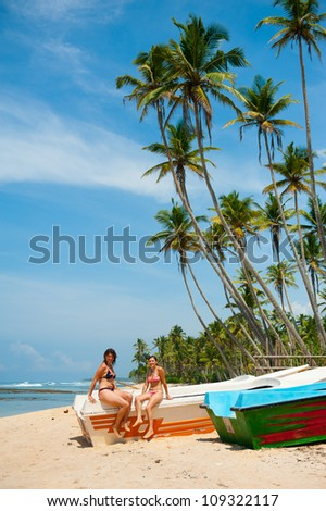 Two women sunbathing on a tropical beach