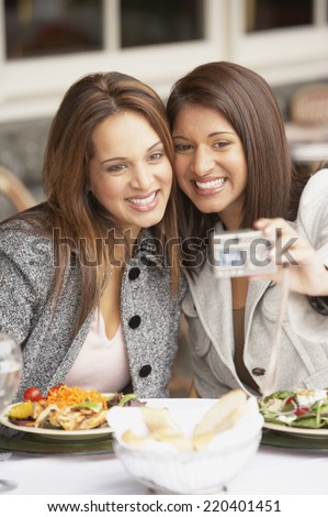 Two women taking a self-portrait at lunch - stock photo