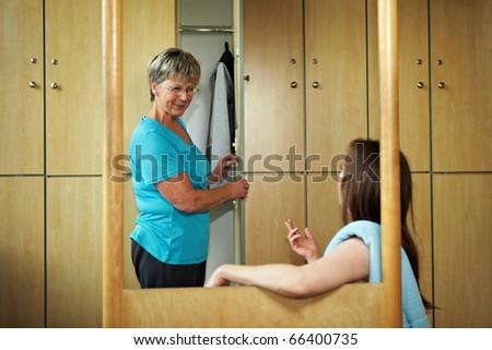 Two women talkin in a locker room - stock photo