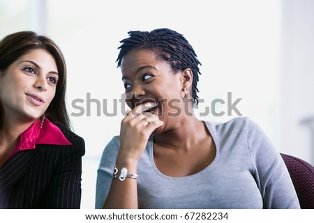 Two women talking and laughing - stock photo
