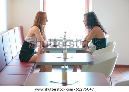 Two women talking in a restaurant, overhead version - stock photo