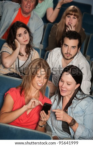 Two women talking in theater with annoyed audience - stock photo