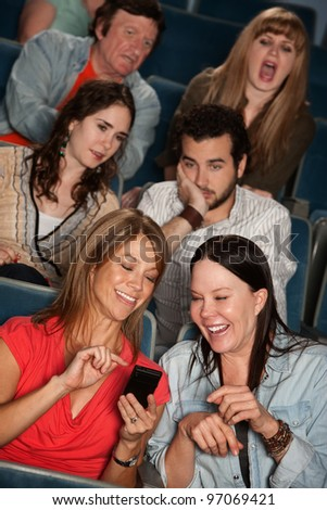 Two women talking in theater with bothered audience - stock photo