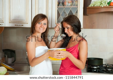 Two  women testing soup from pan at the kitchen - stock photo