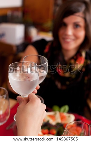 Two women toasting in a restaurant with wineglasses filled with chilled mineral water, focus to the glasses - stock photo