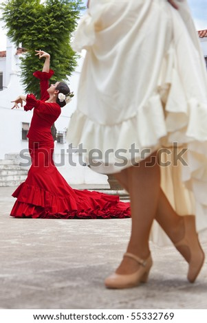 Two women traditional Spanish Flamenco dancers dancing in a town square, the focus is on the dancer in the red dress - stock photo