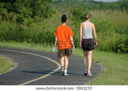 Two women walking along a country path - stock photo