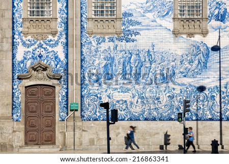 Two women walking along the huge tiled wall of a church in Porto, Portugal, leading to color harmony and typical view of Portugese culture - stock photo