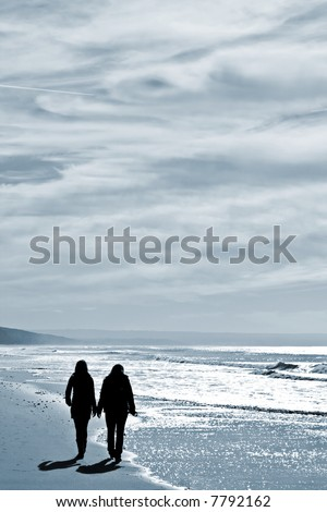 two women walking at the beach in the winter - stock photo