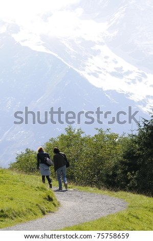 Two women walking in natural park of the grossglockner, the highest mountain in austria. - stock photo
