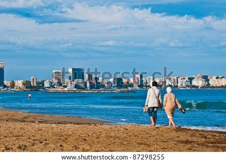 Two women walking on the beach in Alicante - stock photo