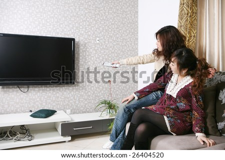 two women watch TV at home