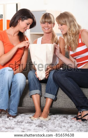 two women watching inside a carton bag in a lounge