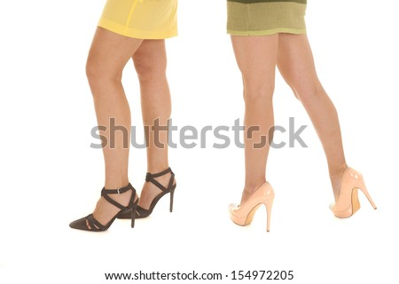 Two women wearing heels and dresses a bottom view of their legs.