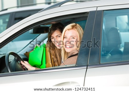 Two women were shopping in a mall or shopping centre and driving home now with their car - stock photo