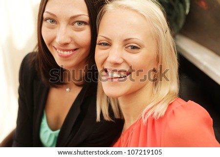 Two women whispering and smiling - stock photo