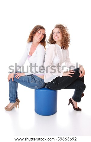 Two women whispering and smiling over white background - stock photo