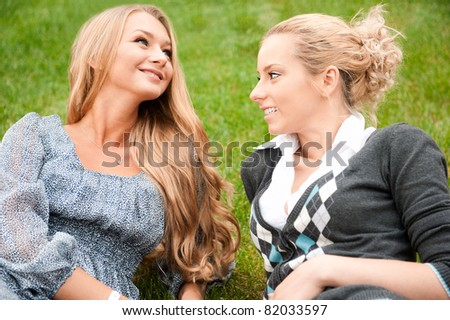 Two women whispering? laughing and smiling at the city park. Sitting on green grass