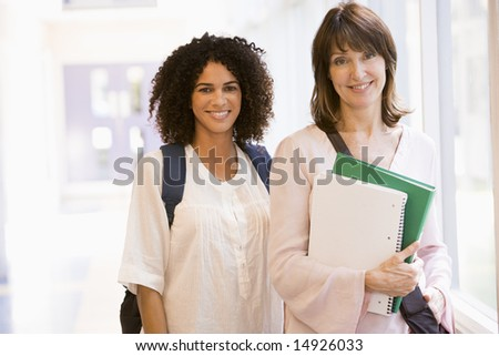 Two women with backpacks standing in a campus corridor - stock photo