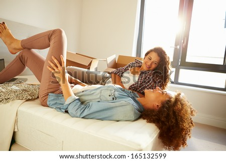 Two Women With Boxes In Bedroom Moving Into New Home - stock photo