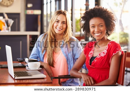 Two women with computer in a coffee shop, portrait - stock photo