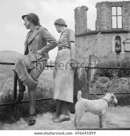 Two women with dog on leash leaning on fence beside ruined building