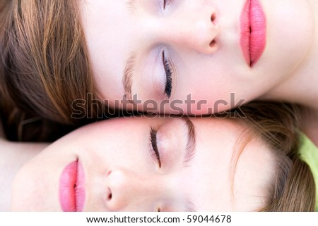 Two women with eyes closed - stock photo