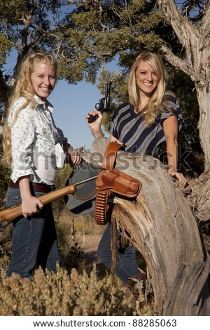 Two women with guns in the out doors with smiles on their faces. - stock photo
