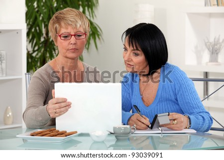 Two women with laptop and calculator - stock photo