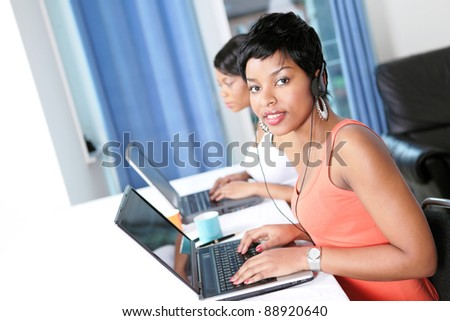 Two women with laptops doing business or trading online with focus on pretty girl looking up - stock photo