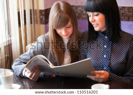 two women with menu in coffee - stock photo