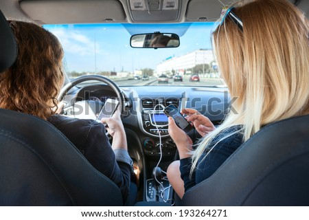 Two women with mobile phones in their hands riding in car
