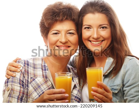 Two women with orange juice. Mother and Daughter - happy family.