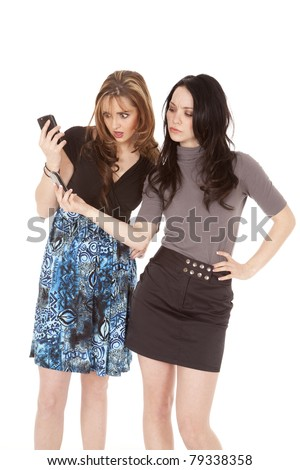 two women with phones, one is showing her phone to her friend, they have shocked expressions on their faces. - stock photo