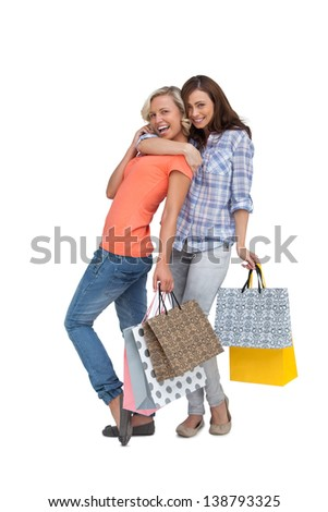 Two women with shopping bags on white background - stock photo
