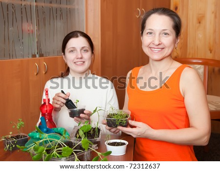 Two women with various seedlings at home