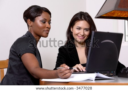two women working at the computer - stock photo