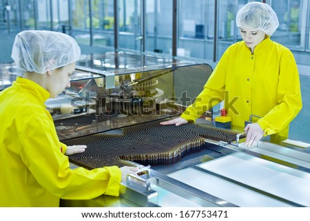 Two Women working at the pharmaceutical factory. Shallow DOFF. See more images and video from this series.  - stock photo