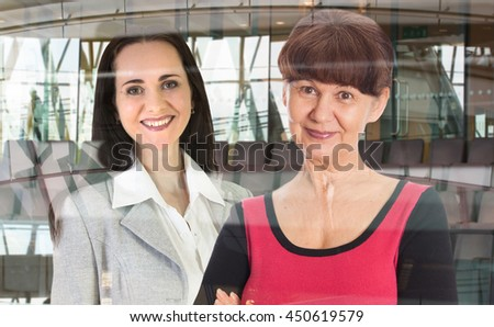 Two women working in  office, portrait against of glass reflection
